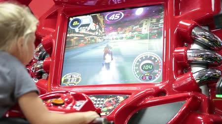 arcada : Young girl playing motorcycle simulation in game center. Gaming zone in Russia