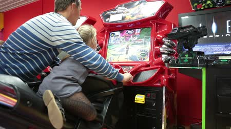 vending machine : Riding on motorbike due coin-op simulator with father help. Young man with small daughter