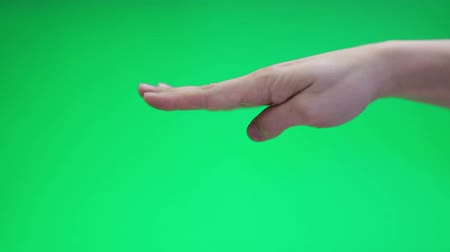 klucz : Hand over green background cutting, gesturing anf making fist. Chroma key