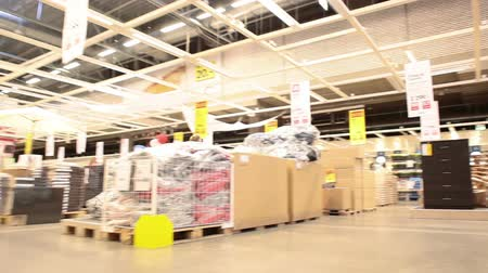 áruk : Moving through the Ikea warehouse with shopping customers Stock mozgókép