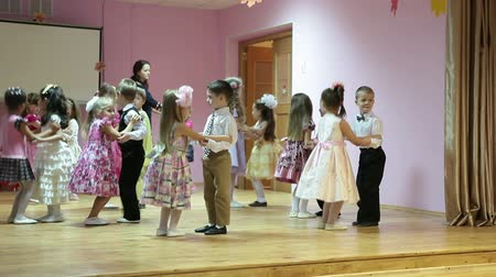 kiddy : Preschooler children dancing in pairs on the kindergarten stage, Russia