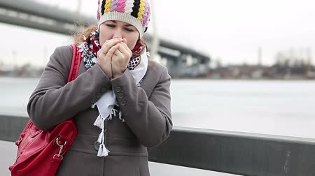 zmrazit : Frozen young Caucasian female warming hands and standing on embankment. Bridge on background Dostupné videozáznamy