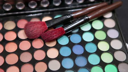pędzel : Make-up brushes laying on color cosmetic palette. Camera rotation Wideo
