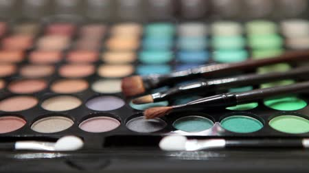 kartáč : Make-up brushes laying on multicolor cosmetic palette. Camera rotation