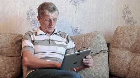 okey : Mature adult showing thumb with tablet PC, sitting on sofa in domestic room Stock Footage