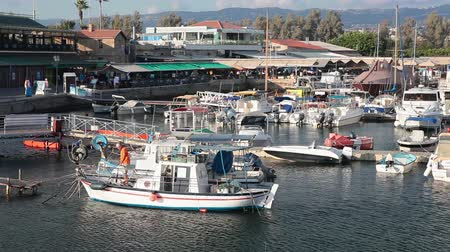 коммерческий : Small motorboats in Paphos harbor with cafe and shops on pier. Cyprus Стоковые видеозаписи