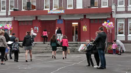 entrance : September, 1. Children going back to school with parents in Russia. First time in school with flowers. Schoolyard with entrance