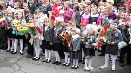 идущий : September, 1. Children going back to school with parents in Russia. Schoolers standing in schoolyard with flowers