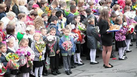 okula geri : Happy first-formers with flowers on school yard on September, 1, Saint-Petersburg, Russia Stok Video