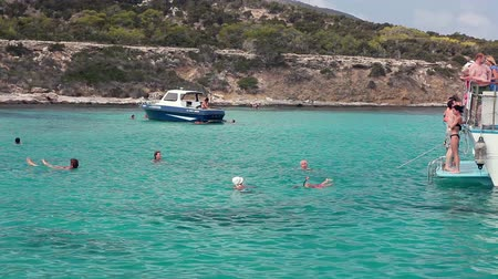 ciprus : Tourists swimming in the blue lagoon, jumping from the deck. Sea cruise along the coast to swim from the boat. Mediterranean Sea, the village of Latchi, Cyprus Stock mozgókép