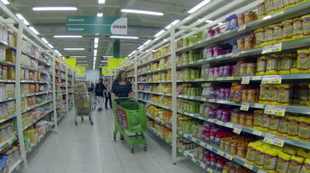 corredor : Woman in supermarket with shopping cart standing near foods, Russian food mall Okey, Saint-Petersburg, Russsia