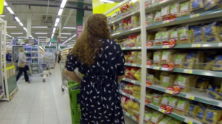 corredor : Woman with grocery trolley in supermarket walking along stands with food. Russian food mall Vídeos
