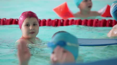 sport dzieci : Children in rubber caps and with swim board standing in swimming pool when training Wideo
