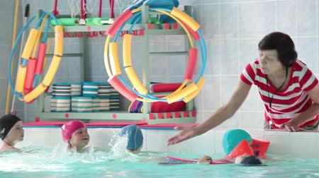 lesson : Mature trainer teaching child to swim in swimming pool