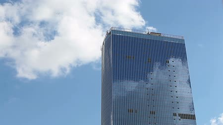 ângulo : Modern mirrored building and fast moving white clouds on the blue sky