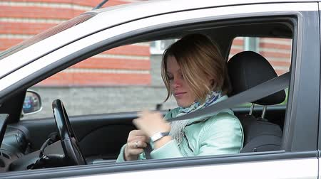 ремень : Young Caucasian woman sitting in car and fastening safety belt.