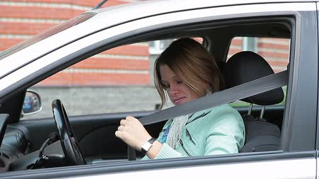 yönlendirmek : Young Caucasian woman sitting in car and fastening safety belt.