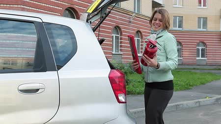 trójkąt : Young female driver putting a fire extinguisher and warning triangle in the boot of the car, closing it, and sitting inside