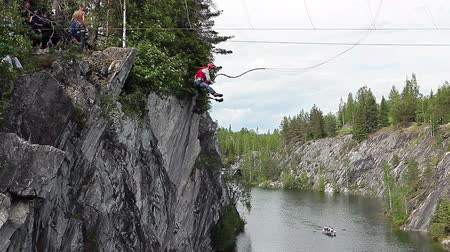 fall down : Extreme bungee jump from the rock to the flooded marble quarry circa June in Ruskeala, Karelia, Russia