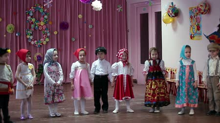 anaokulu : performance on the kindergarten`s stage dedicated to the holiday of International Womens Day (March, 8). Children artists and teacher playing. Russia Stok Video