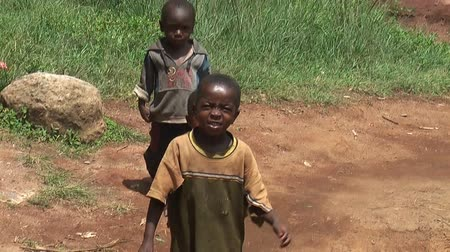 yoksulluk : African children stand near huts and look with interest at camera Stok Video