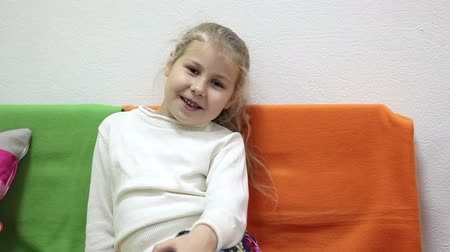 speach : Young girl hase interview when sitting on color sofa, without sound