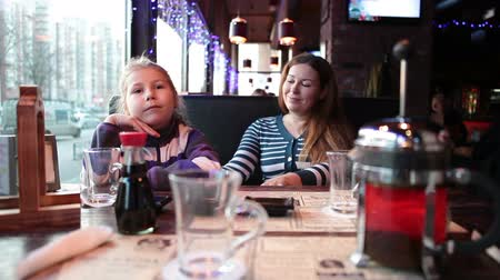 bekleme : Hungry six years girl with mother waiting for food in restaurant, sitting with drinks on the table