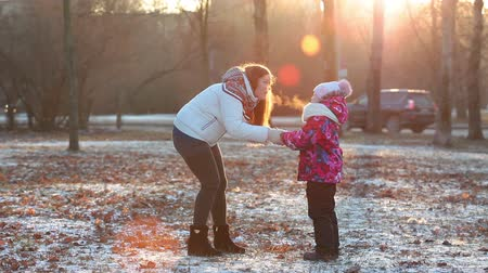 согревание : Frozen mother and child warming together, running and breathing on hands. Park at winter, sundown