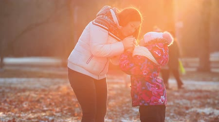 small park : Bright evening sun light with woman breathing on child frozen hands at winter season Stock Footage
