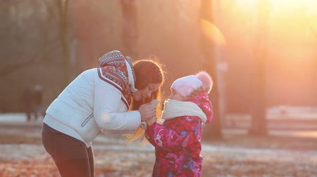 congelado : Mother breathes on daughter frozen hands when walking on park at winter sunset