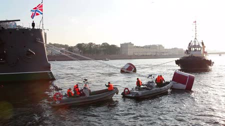hawser : ST. PETERSBURG, RUSSIA - SEPT, 21, 2014: Motorboats with riggers are near Aurora`s tow-ropes on Neva river. Tugging to Kronshtadt for repair works. Cruiser Aurora is symbol of Revolution of 1917 year