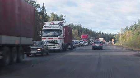 wayside : Car is going forward standing in traffic jams vehicles. Road repair on Scandinavia route, Russia