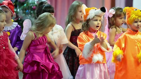 śpiew : Small children standing on the stage in beauty costumes and singing songs to parents. Christmas eve party in Russia
