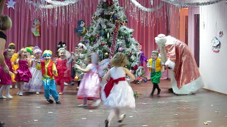 przedszkole : Santa Claus and Snow-maiden girl playing with children on the stage in Russian kindergarten