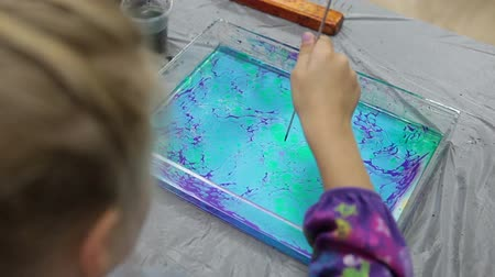 aqueous : Child making red circle with stick on marble color pattern. Ebru art is drawing by oil over water