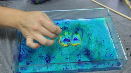 sulu : Female hand drawing butterfly wings from color flower on water surface