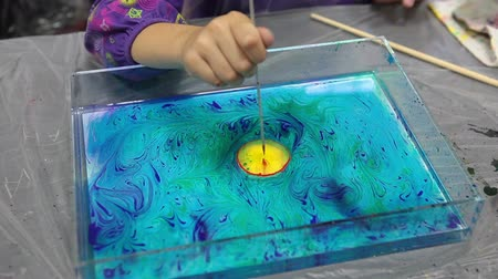 aqueous : Yellow paint inside red for circle appearing on water surface. Ebru drawing