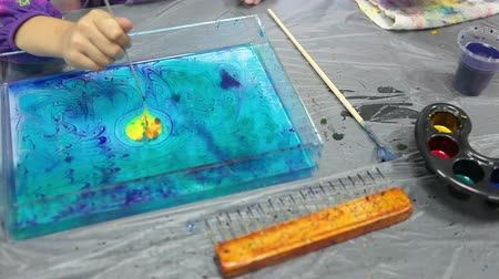 aqueous : Child drawing on water surface with stick. Ebru art