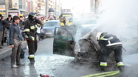 extinguishing : Burned car owner with firefighters standing near vehicle remains on city street on November 11, 2012, in Saint-Petersburg, Russia