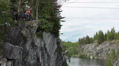 aşağı : Man ready to jump with bungee rope from rock, Ruskeala Park with green marble quarry, Karelia, Russia