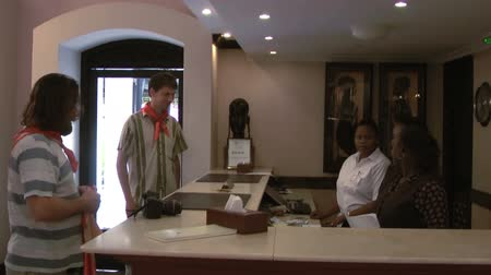 lounge : Caucasian people presenting necktie for hotel staff on reception, African women. Tanzania, Africa Stock Footage