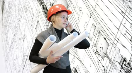 mérnök : Woman architect talking by cellphone and holding blueprints, black-and-white drawings background
