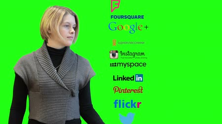 hlavní stránka : SAINT-PETERSBURG, RUSSIA - CIRCA NOVEMBER, 2014: Young Caucasian woman spinning column with social media icons as twitter, facebook, linkedin, Instagram. Skype main page at the end, green screen