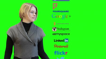sosyal : SAINT-PETERSBURG, RUSSIA - CIRCA NOVEMBER, 2014: Young Caucasian woman spinning line of social media icons as twitter, Instagram, linkedin, skype. Facebook main page at the end, green screen