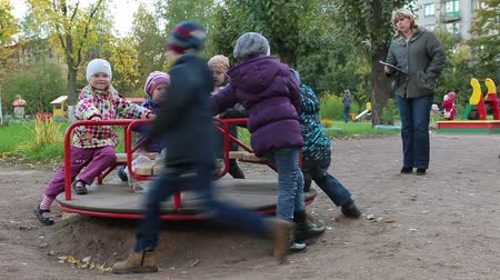 przedszkole : Rotating roundabout with happy kids and teacher slowing the spinning