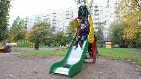 yards : Happy kids riding on children`s slide on playground. Russian kindergarten