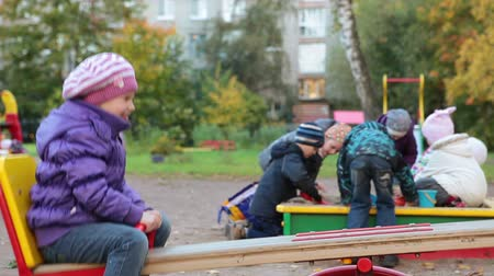 preschool : Girl sits on seesaw and swings up and down by pushing the ground with her feet. Kids play in sandbox Stock Footage