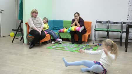 przedszkole : Two mothers sitting on sofa and girl playing around in domestic playroom