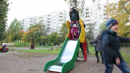 kreş : Cheerful kids riding on children`s slide on playground. Russian kindergarten Stok Video