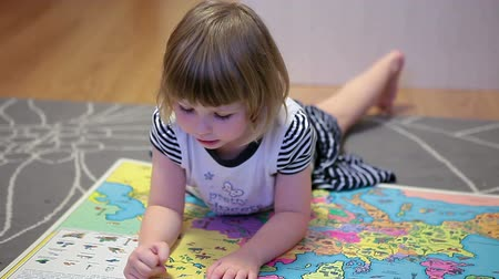 sitting room : One little girl with world map laying on the floor and showing different countries
